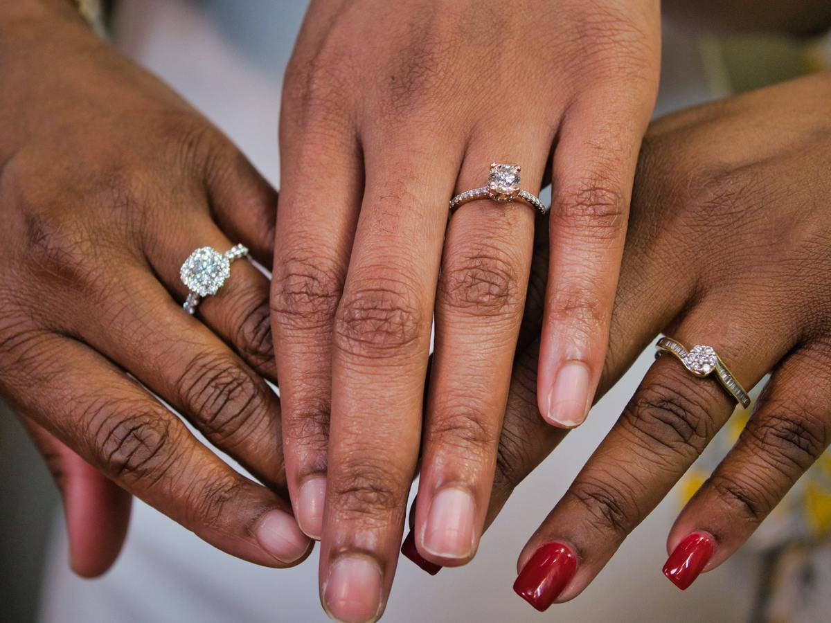 Three women hold out their hands and show off their diamond engagement rings