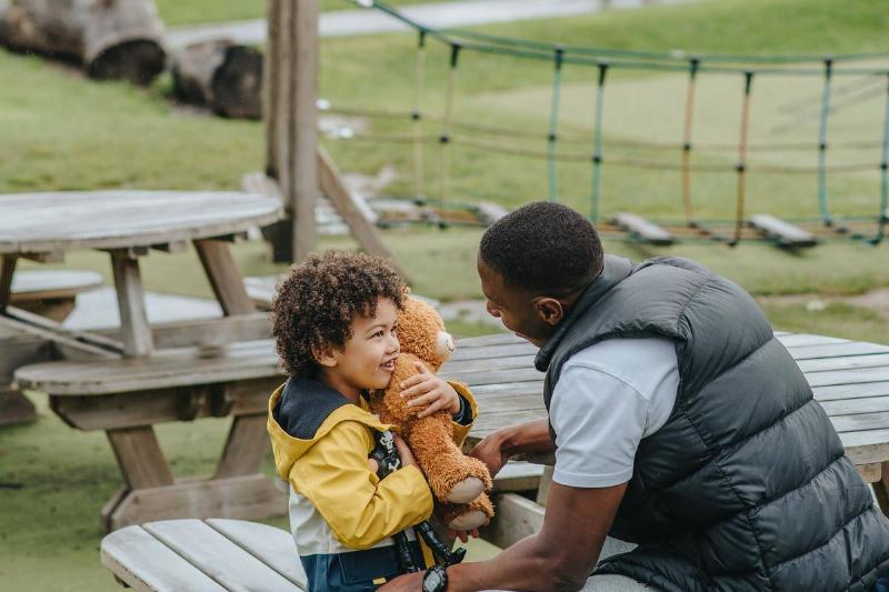 Father and son play in the park while the son holds a teddy bear
