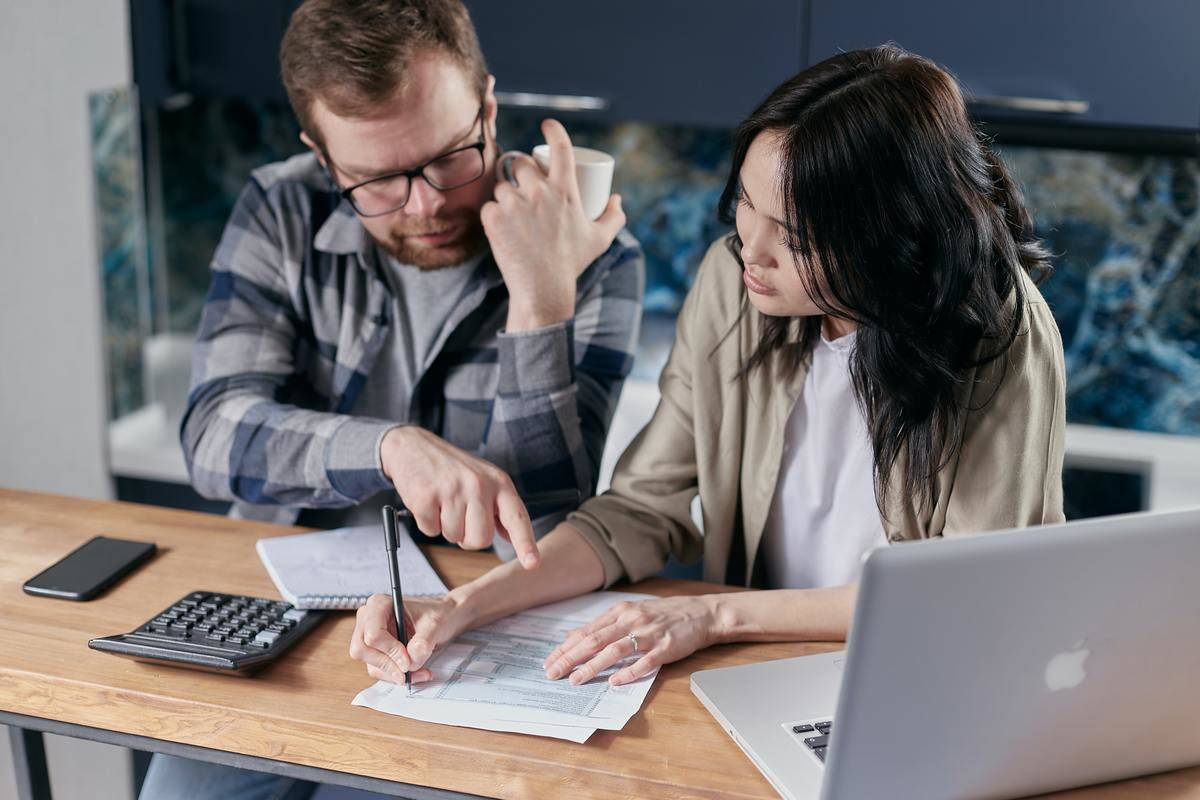 Couple financial planning at table with calculator