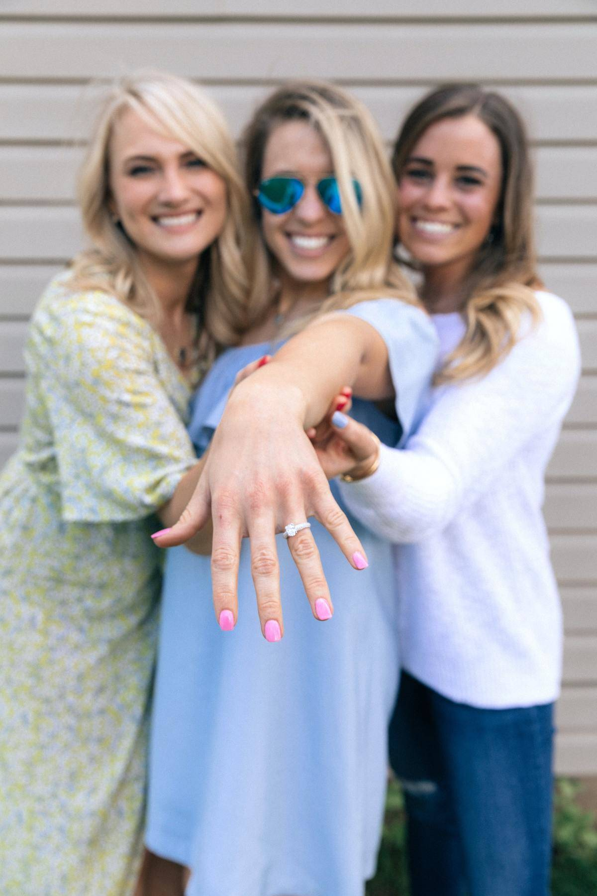 Woman shows off engagement ring, friends smile alongside