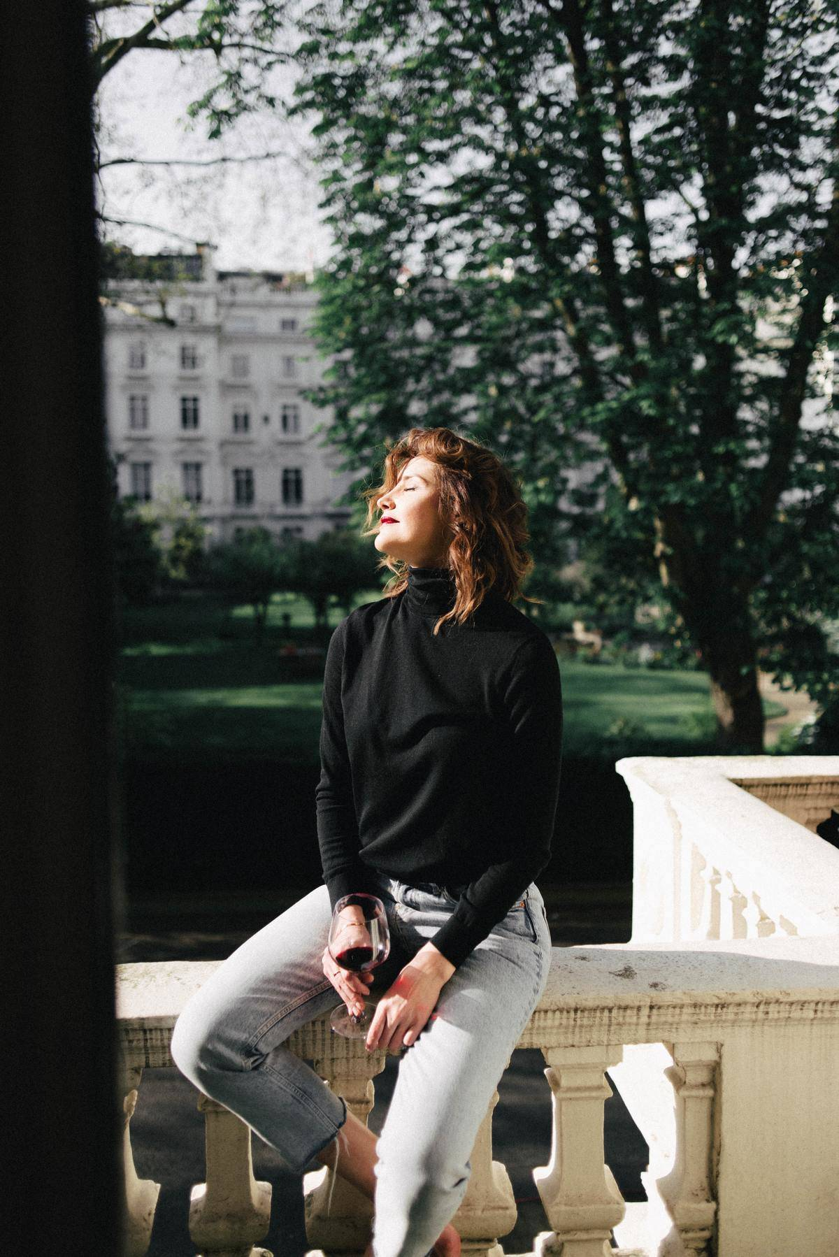 Woman sitting alone on balcony in sunshine looking happy