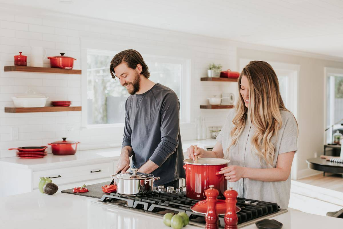 Couple cooking in kitchen with red cookware