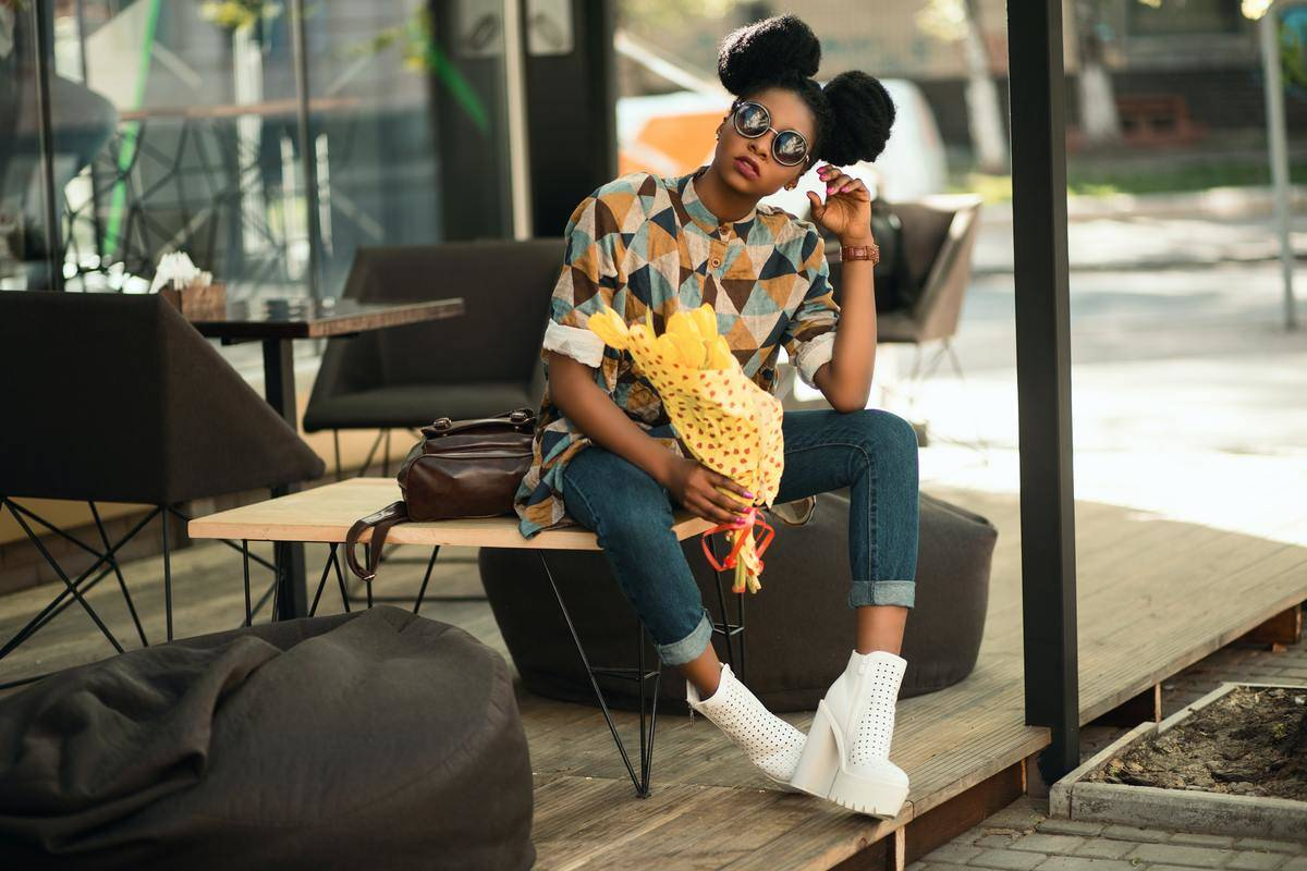 Woman in bright yellow patterned shirt sits alone