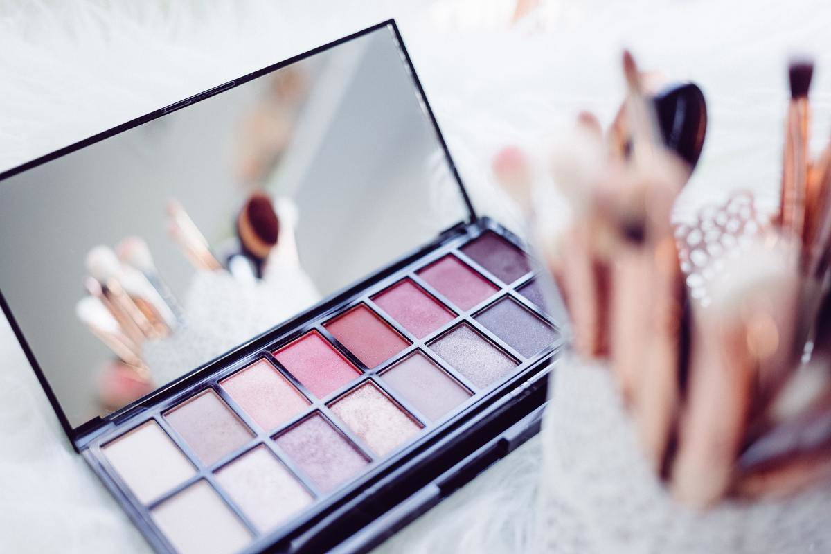 Makeup palate of neutral, pink, and purple eyeshadows and a container of makeup brushes