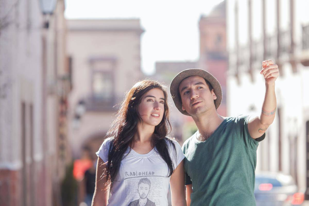 Man points at something in the distance while woman looks at what he's talking about