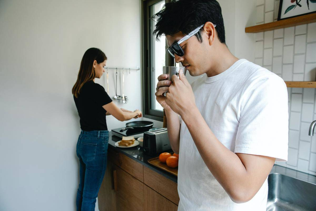 Woman and man in kitchen, woman cooks, man drinks coffee