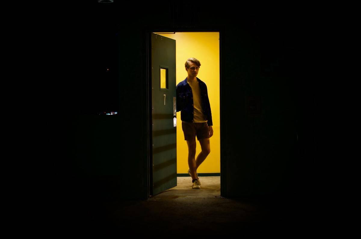 Man opening doorway into dark room