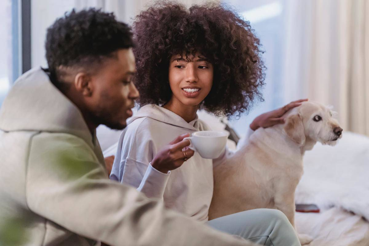 Man and woman sit on couch, she has tea and strokes dog