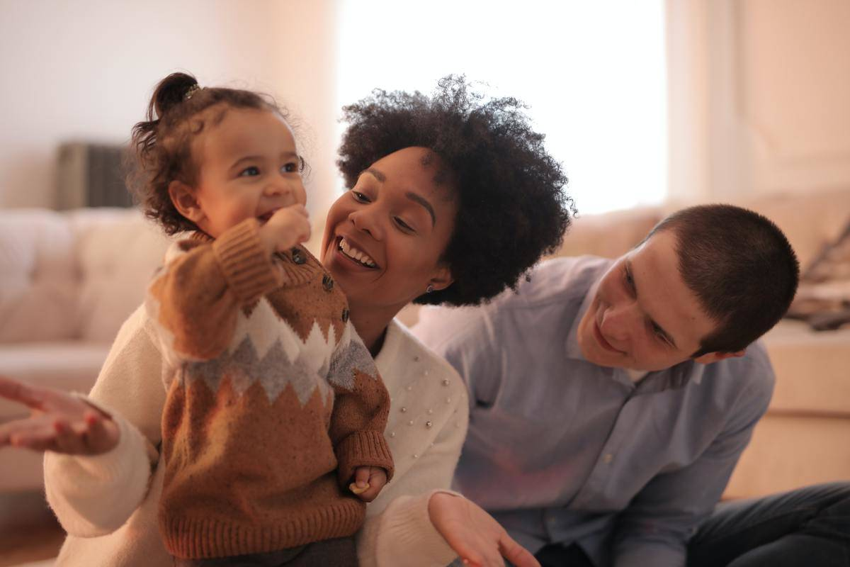 Mom and small toddler and partner behind, all seated on living room floor