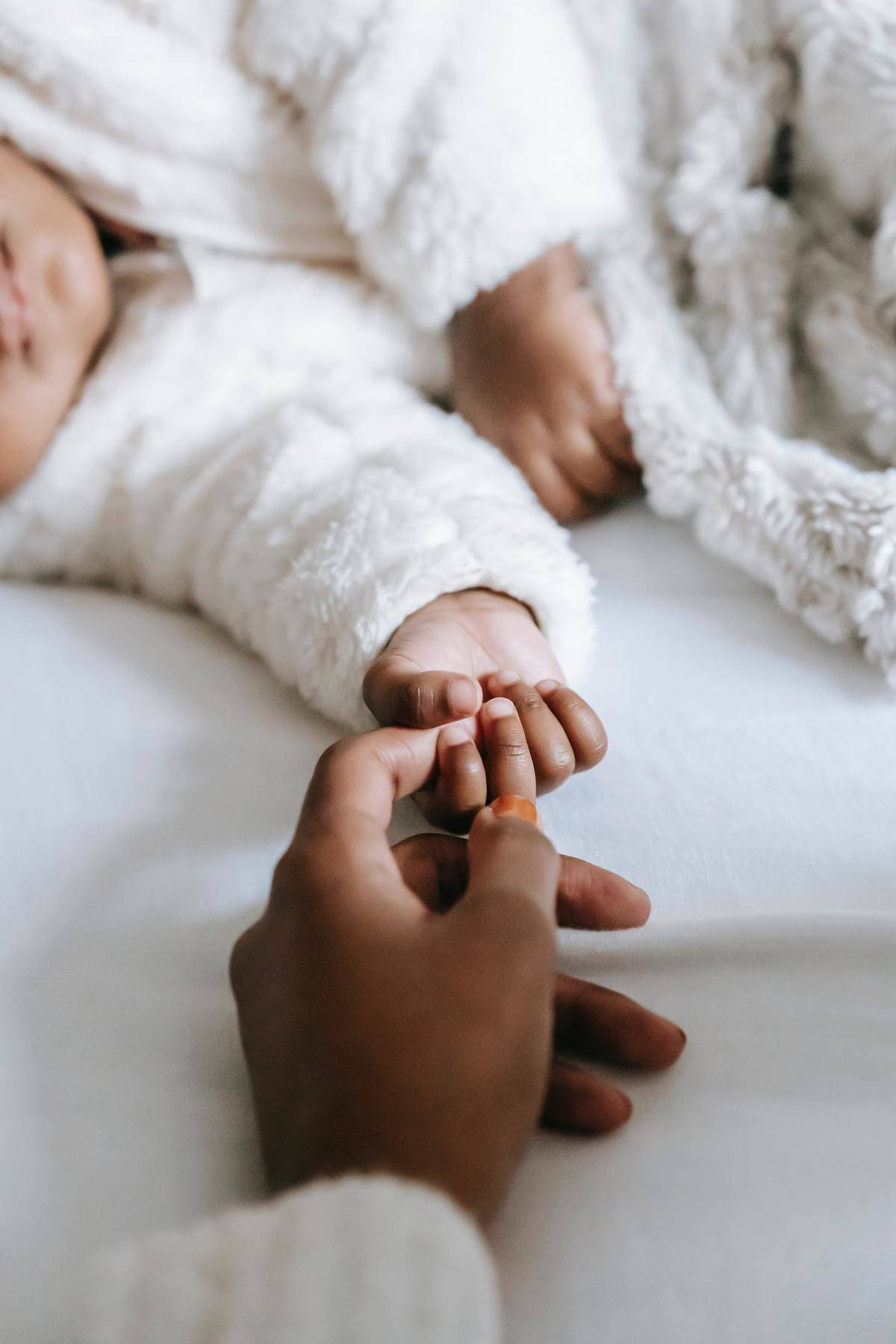 Mother holds infant's tiny hand