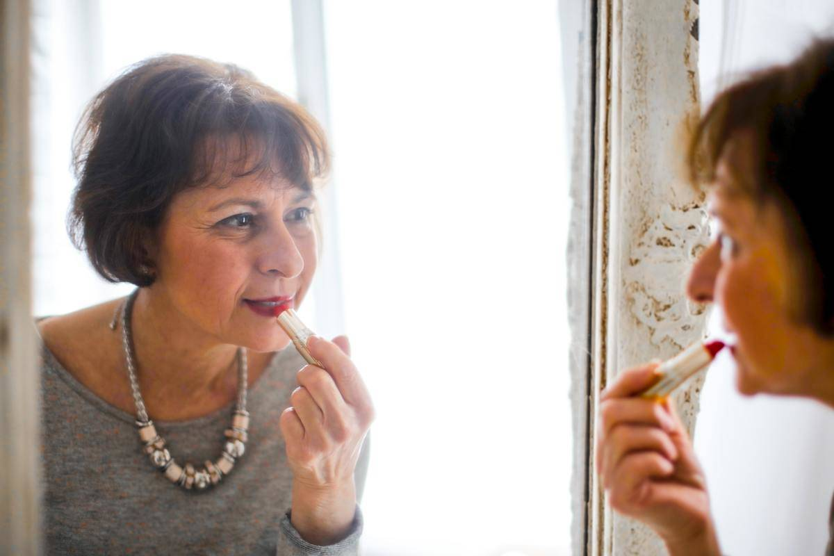 Older woman applies red lipstick in the mirror