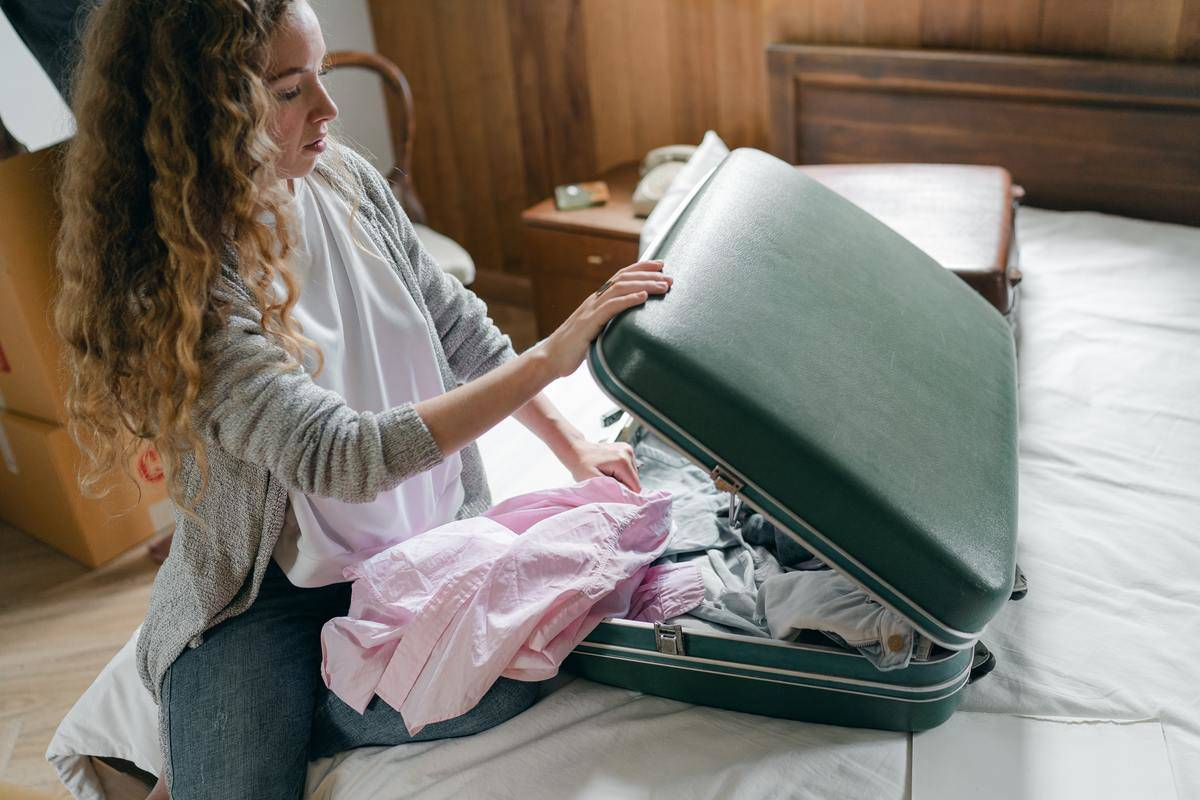 Woman packing bag on bed