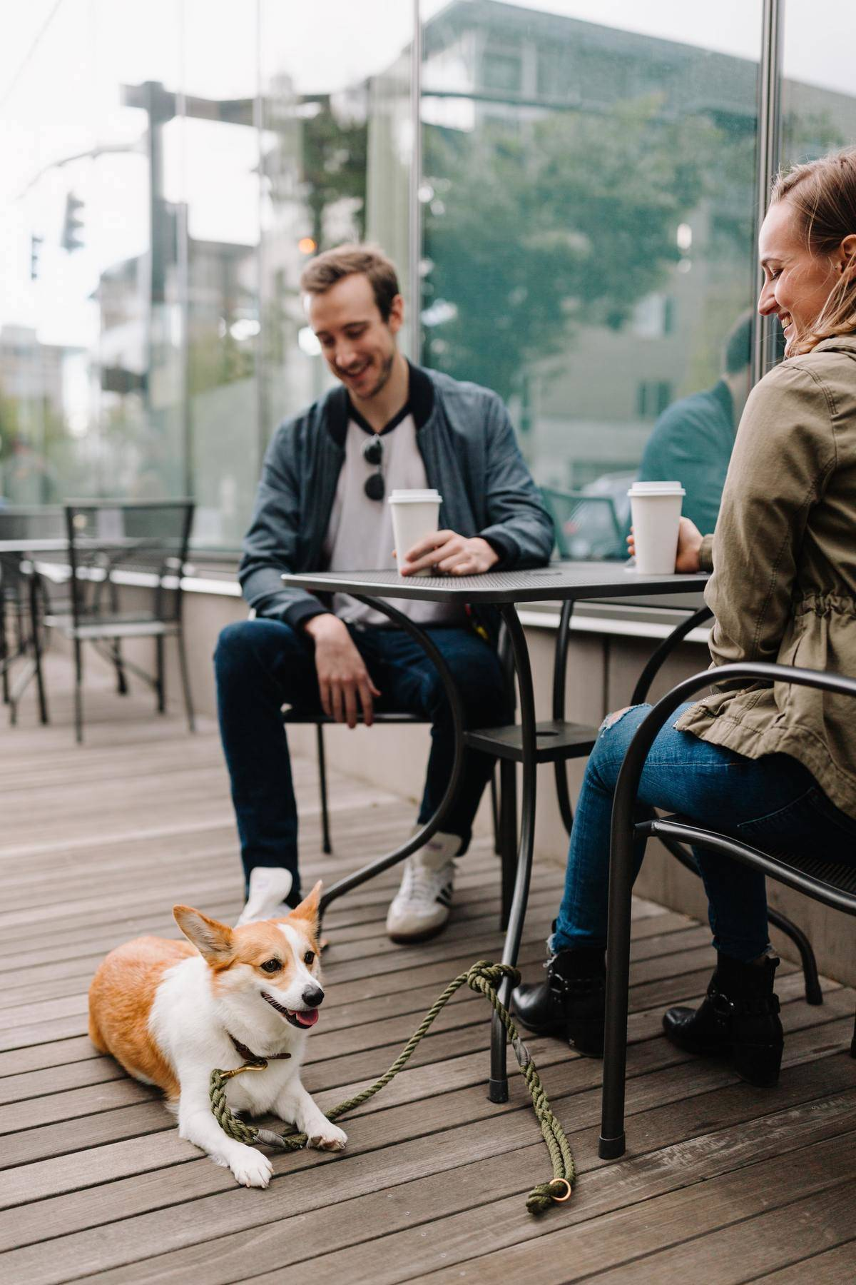 Couple sit on patio for date with corgi dog at their feet