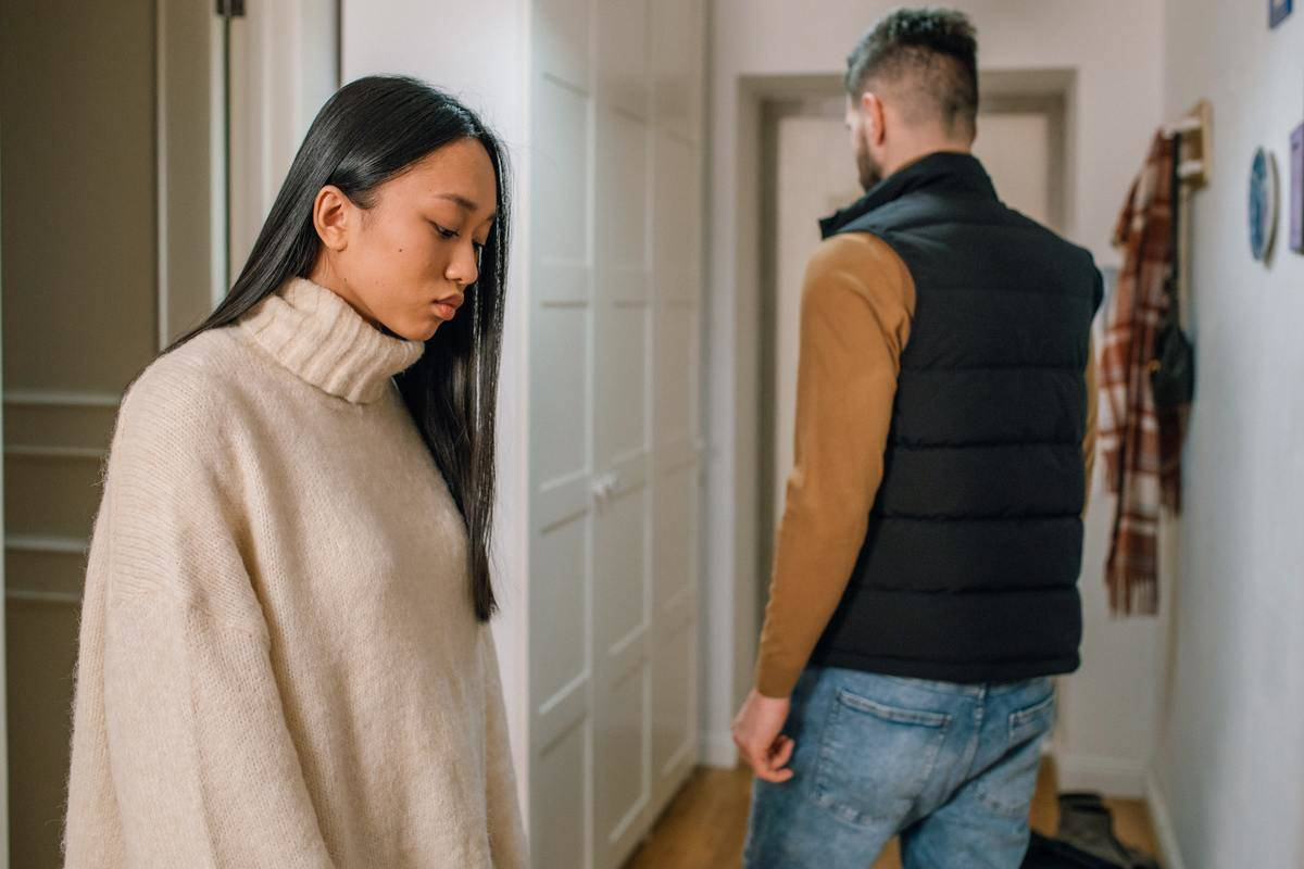 Woman and man stand in hallway facing away from each other