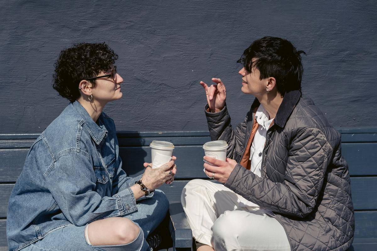 People talking on bench with coffees