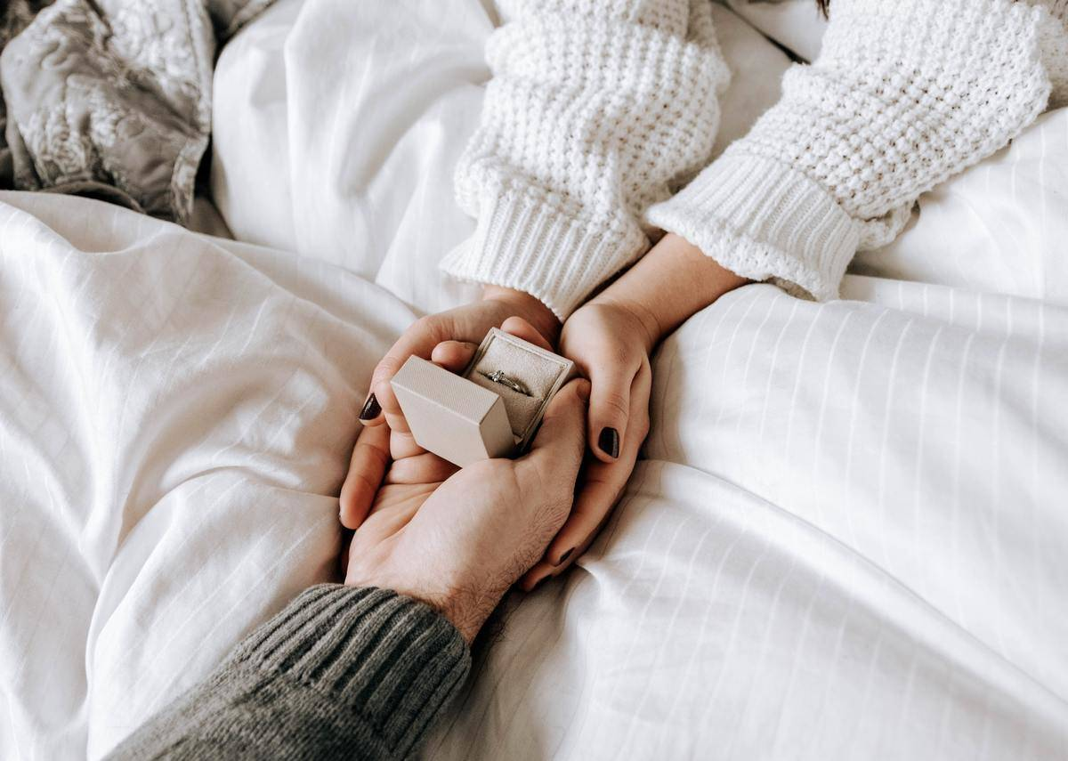 Woman opens ring box in bed being handed to her by man; only their arms are seen