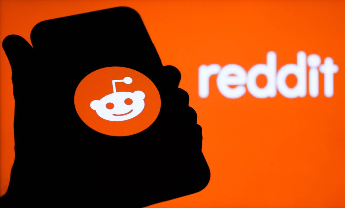 Reddit logos displayed on a phone screen and in the background are seen in this illustration photo taken in Poland on February 1, 2021