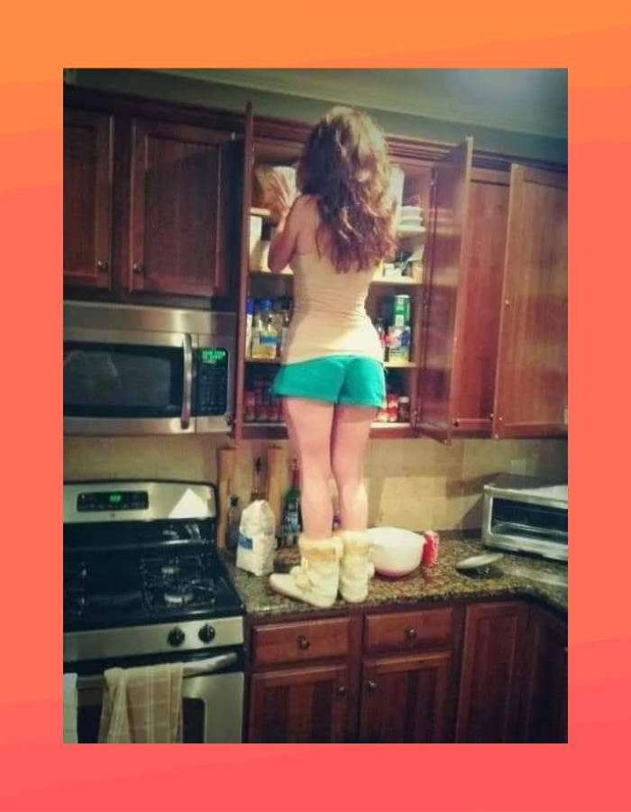 Short girl climbs up on a countertop to reach something off the top shelf