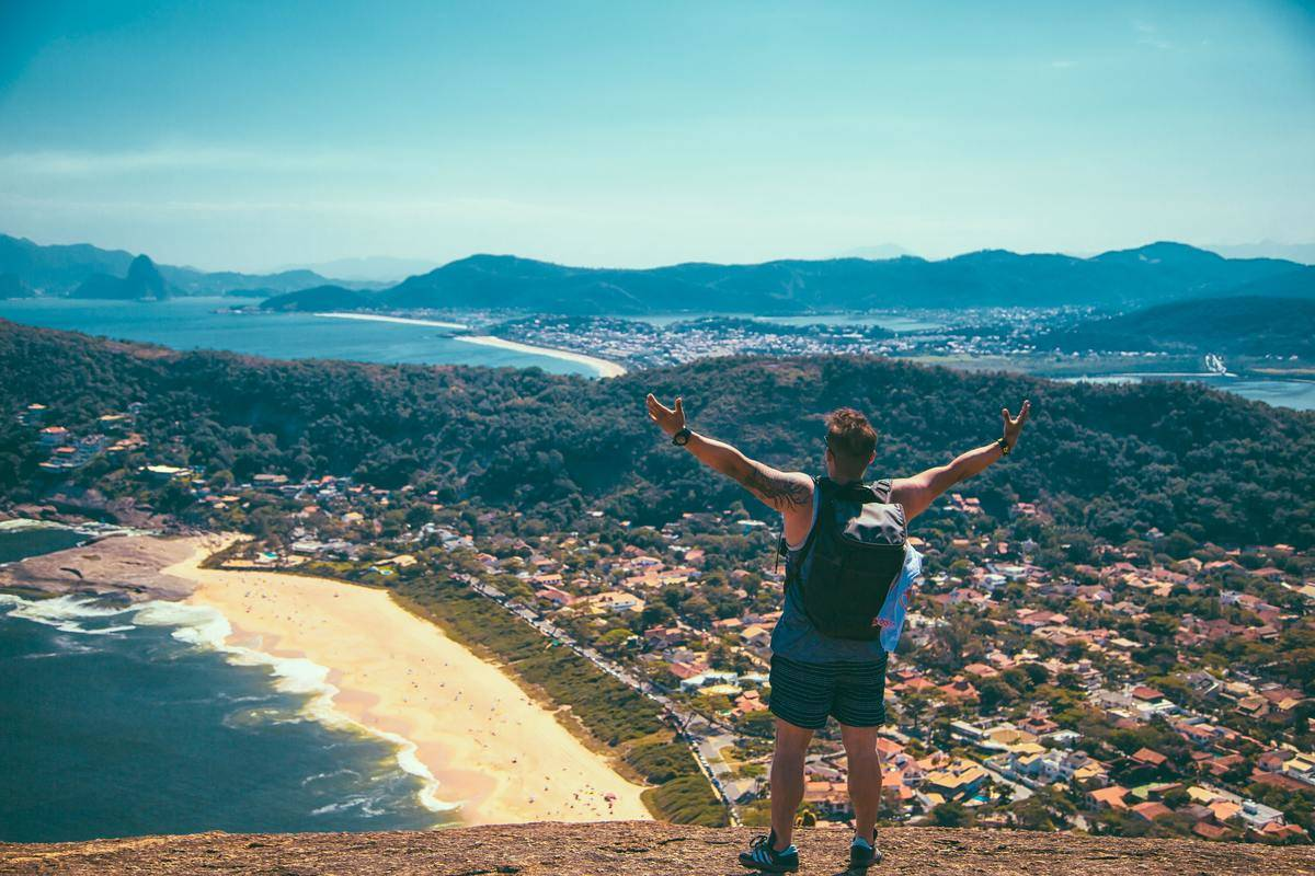 Man stands atop a hill and overlooks a small beachside town