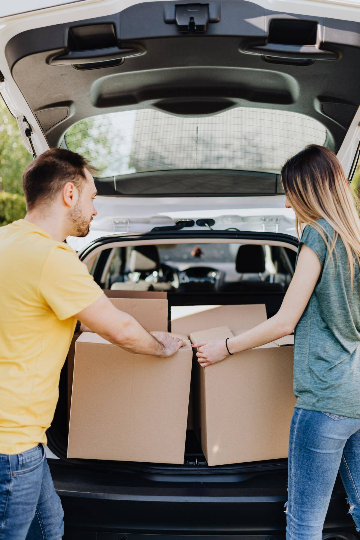 Couple unload cardboard boxes from trunk of car