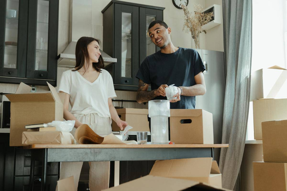 Man and woman in kitchen of house unpacking boxes