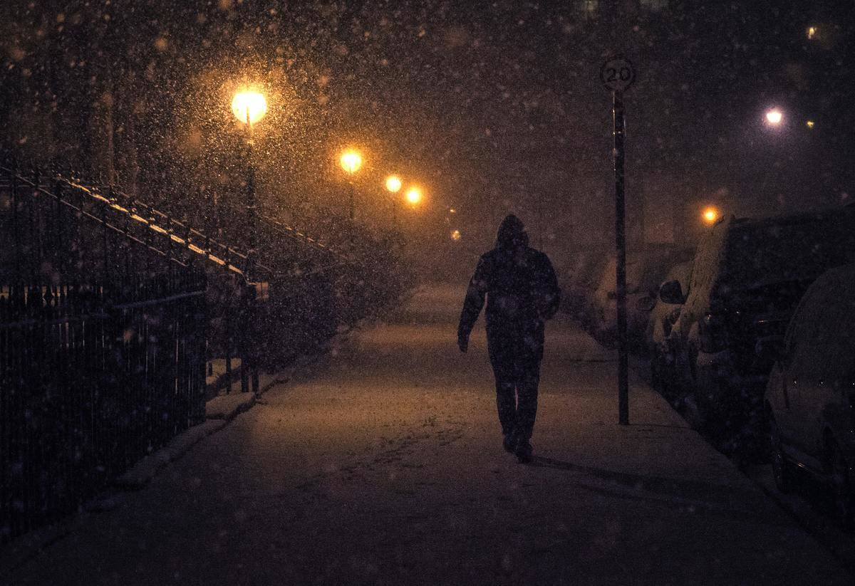 Man walks adown sidewalk in the dark during a snowfall