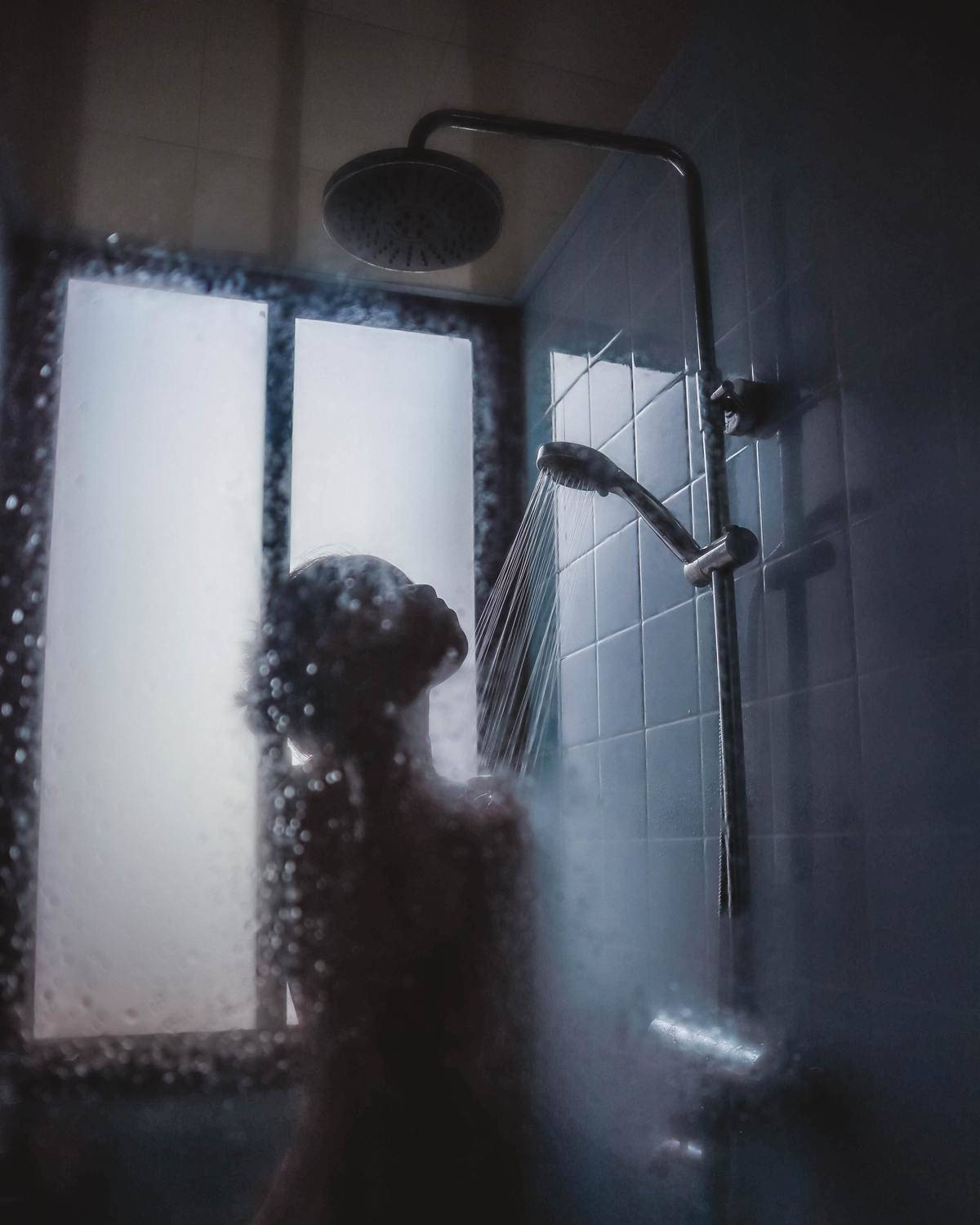 Woman in shower with water running