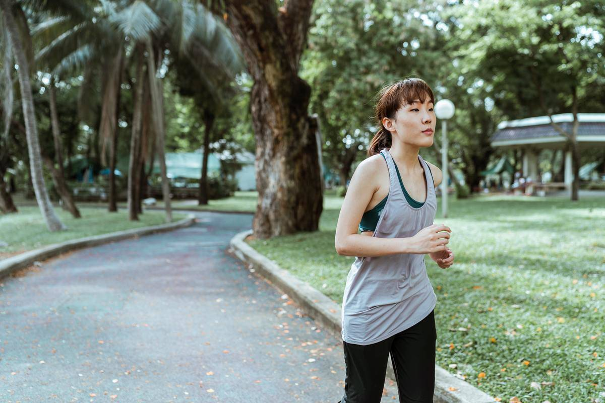 Woman jogging on park path alone