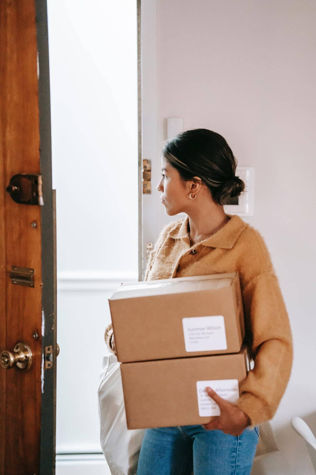 Woman holding package looking in open door