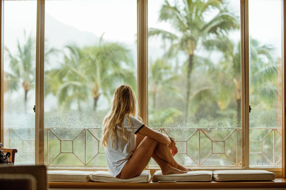 Woman sits at large bay window looking out at palm trees