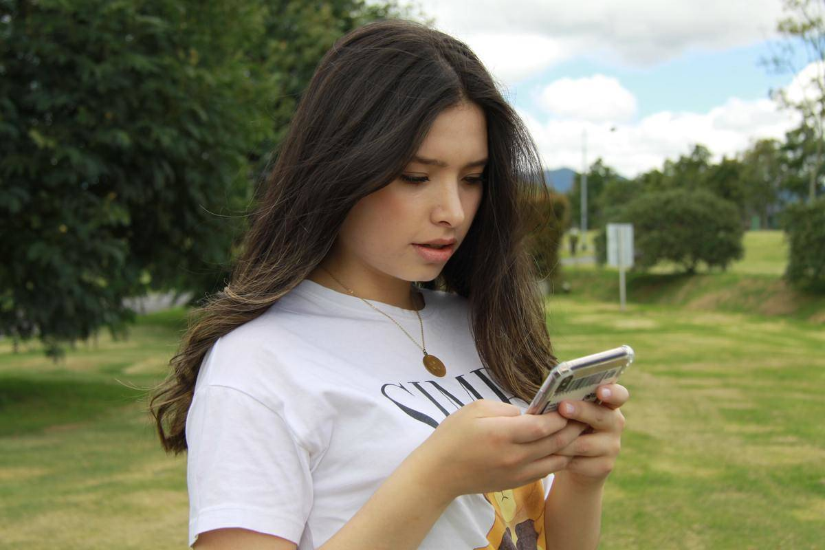 Woman stands in a park and looks at her cell phone