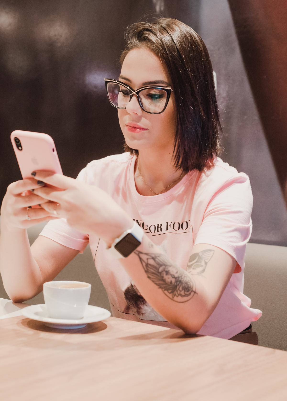 Woman sits in front of coffee scrolling on cell phone