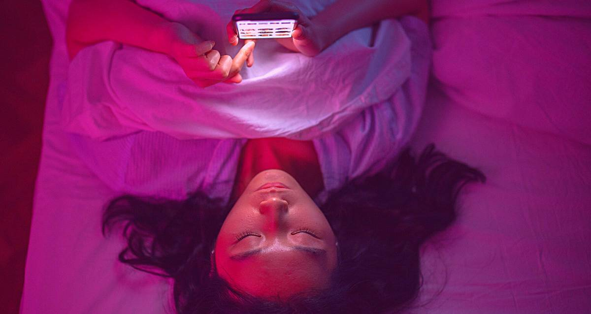 Woman in pink on phone in bed