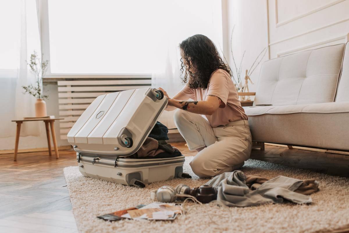 Woman packs suitcase on living room floor