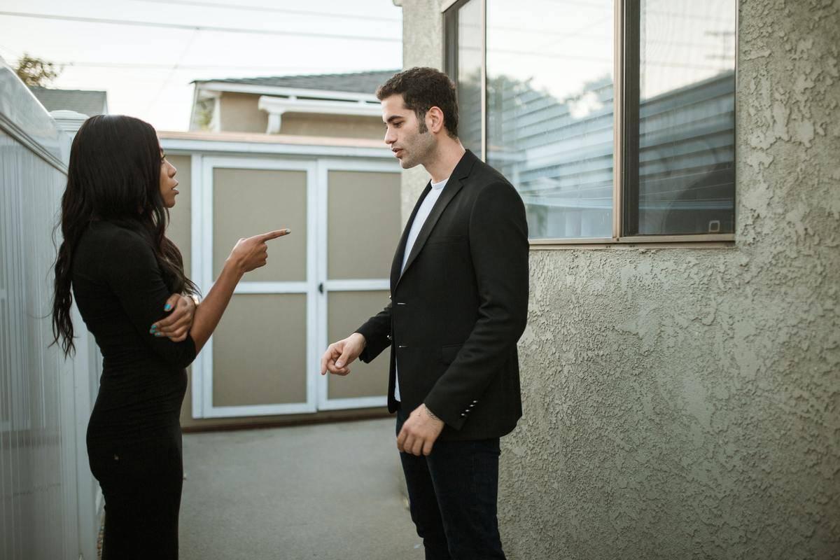 Woman pointing at man talking to him