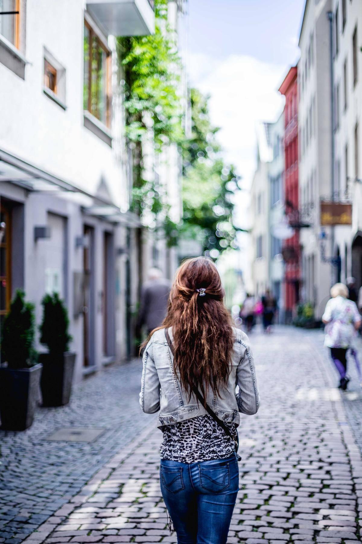 Woman walking down cobblestones alone