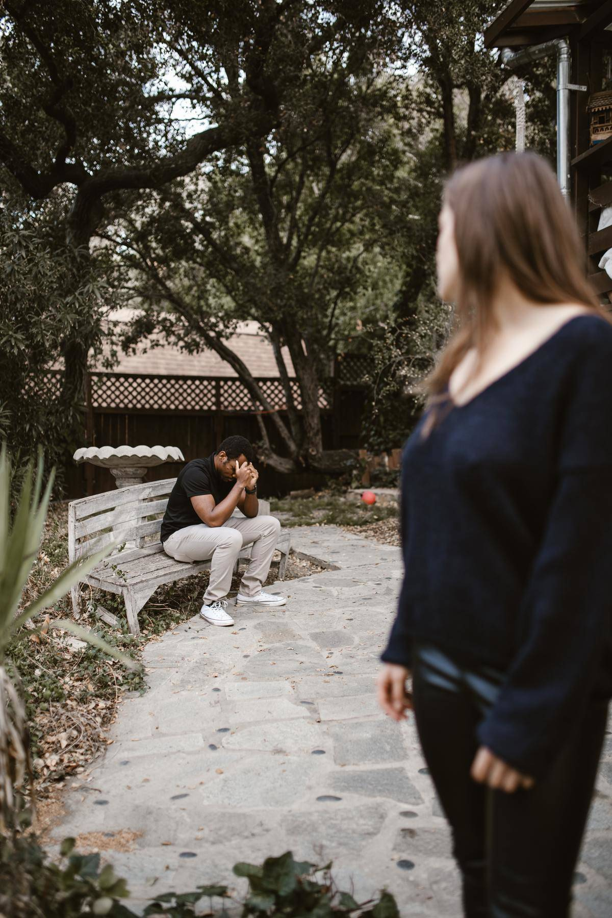 Woman walking away from man who is seated on bench