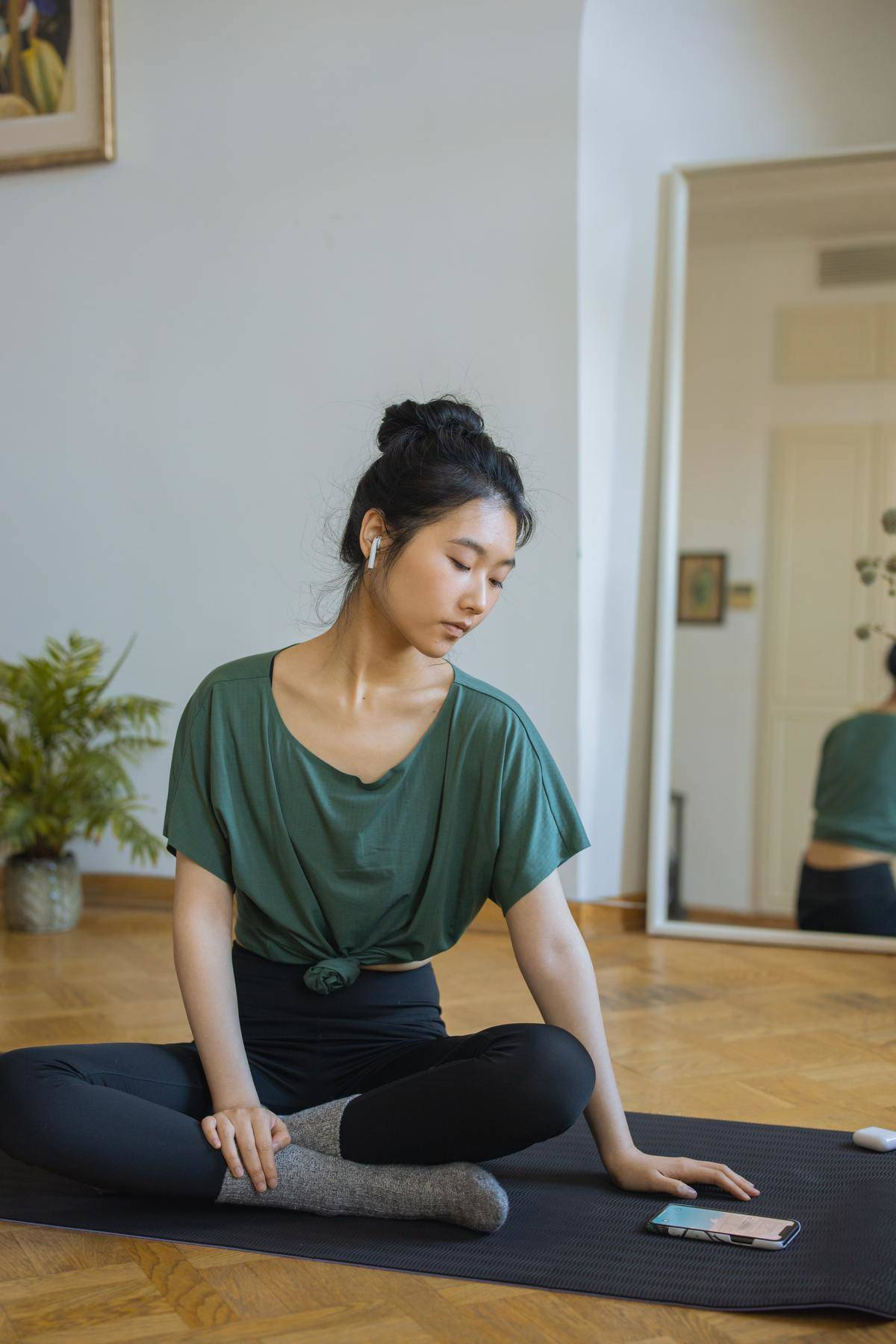 Woman sitting on yoga mat looking down at phone