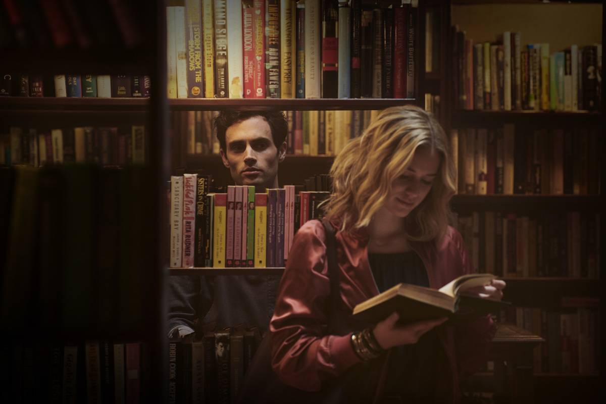 man staring at woman through bookshelves from TV show You