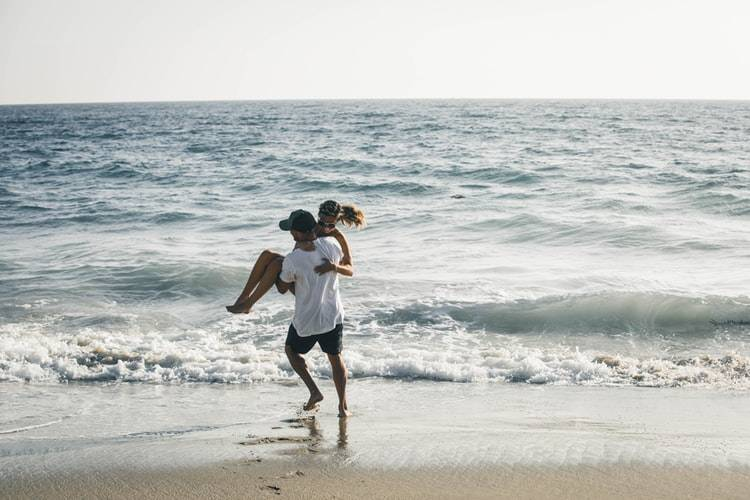 man carrying woman into the water at the beach