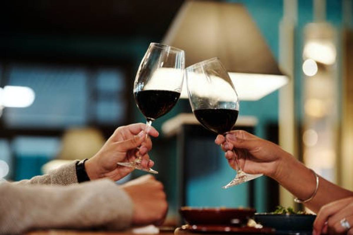 two people clinking wine glasses at dinner