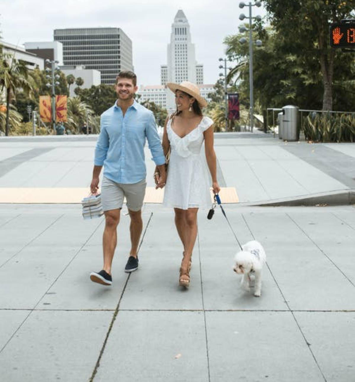 couple walking together holding hands, woman is walking a dog on a leash
