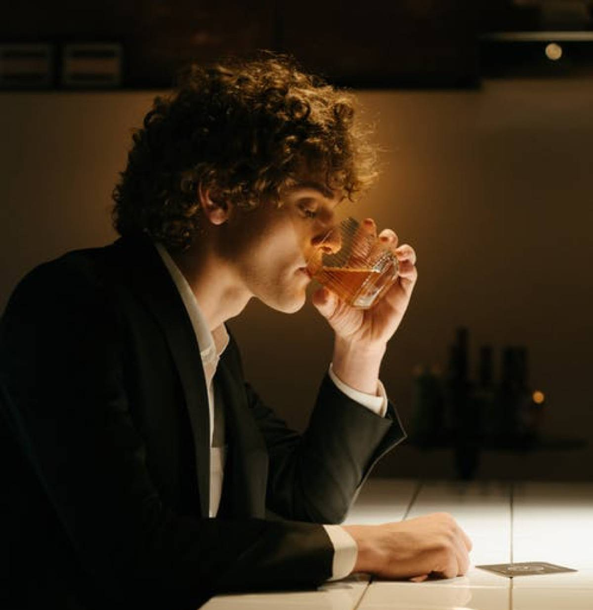 curly haired man drinking alone at bar