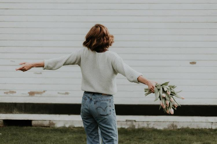 woman holding flowers with her arms outstretched