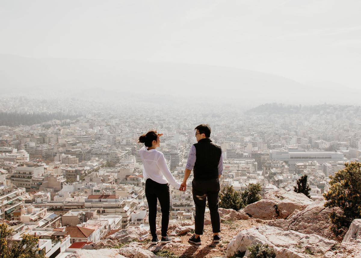 man and woman hold hands standing on a cliff overlooking the city