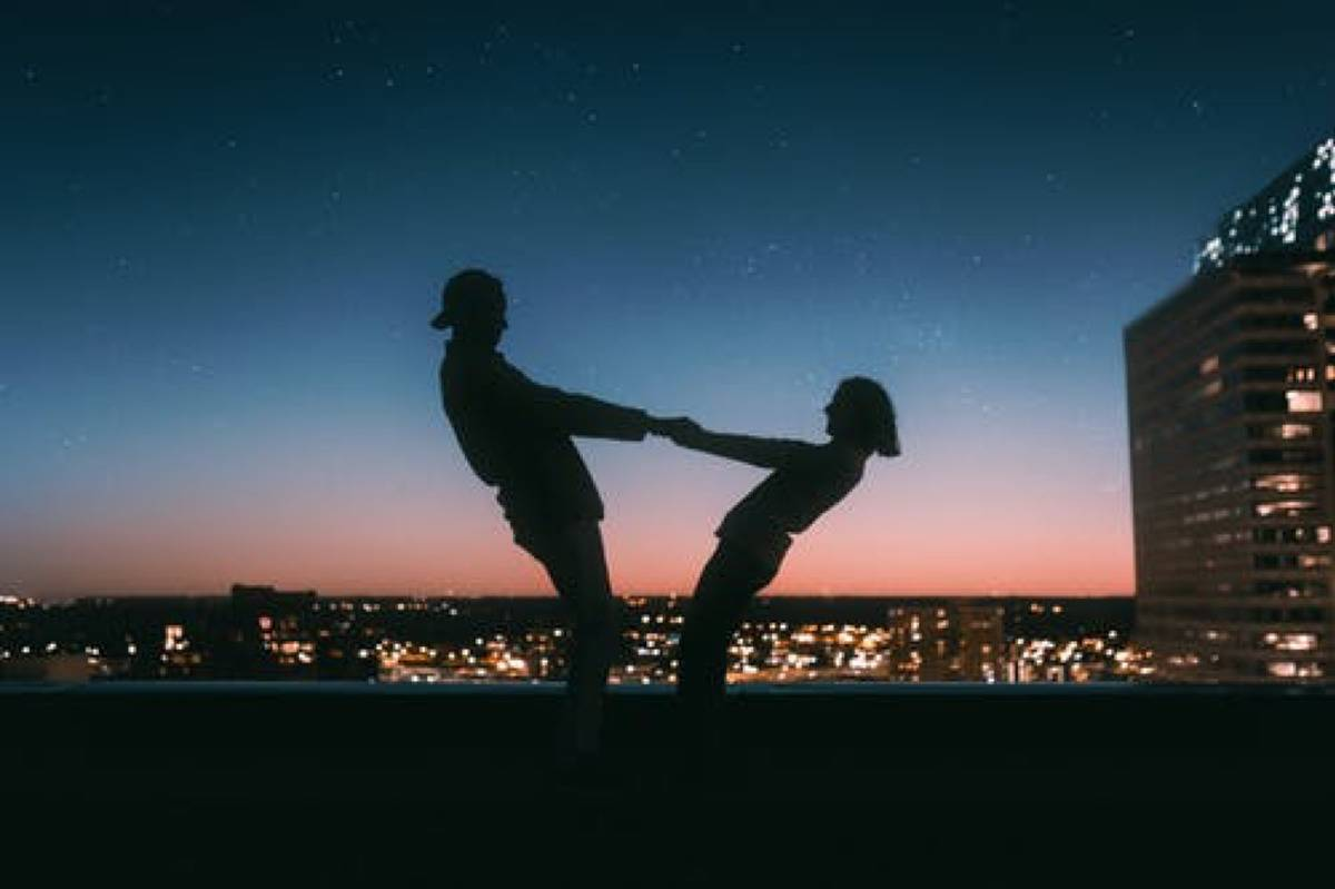 couple holding hands at night on a rooftop overlooking the city