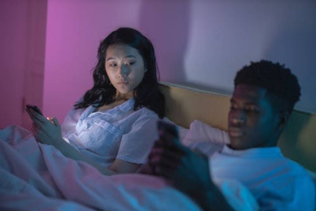 man and woman in bed, woman looking over at man's phone