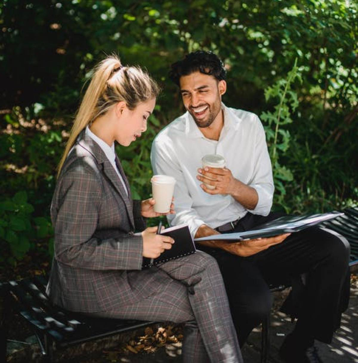 man and woman sitting outside together holding coffee