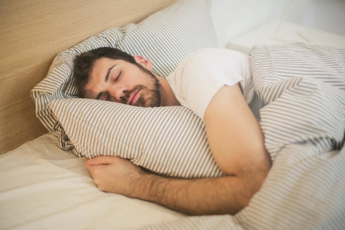 man in bed hugging pilow with eyes closed