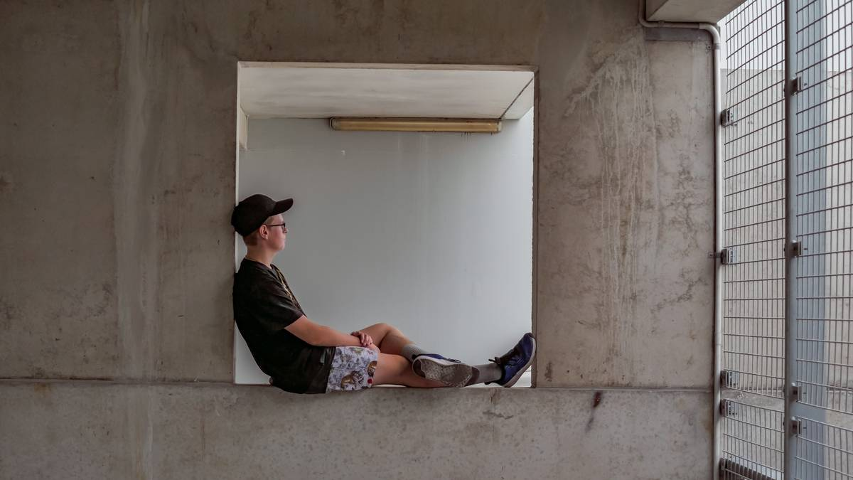 man sitting on open square in concrete wall
